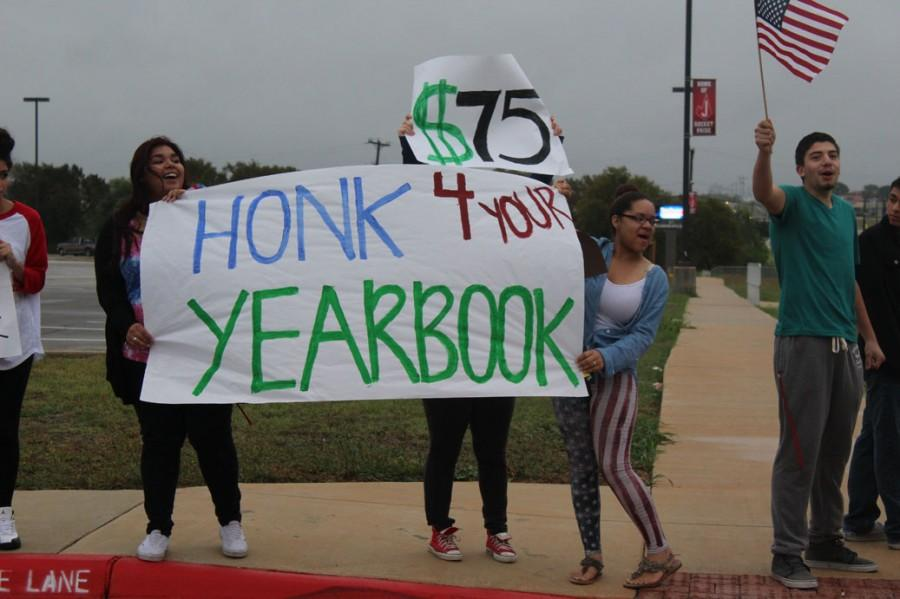 Students+stand+in+front+of+the+school+to+promote+the+sale+of+the+yearbook.