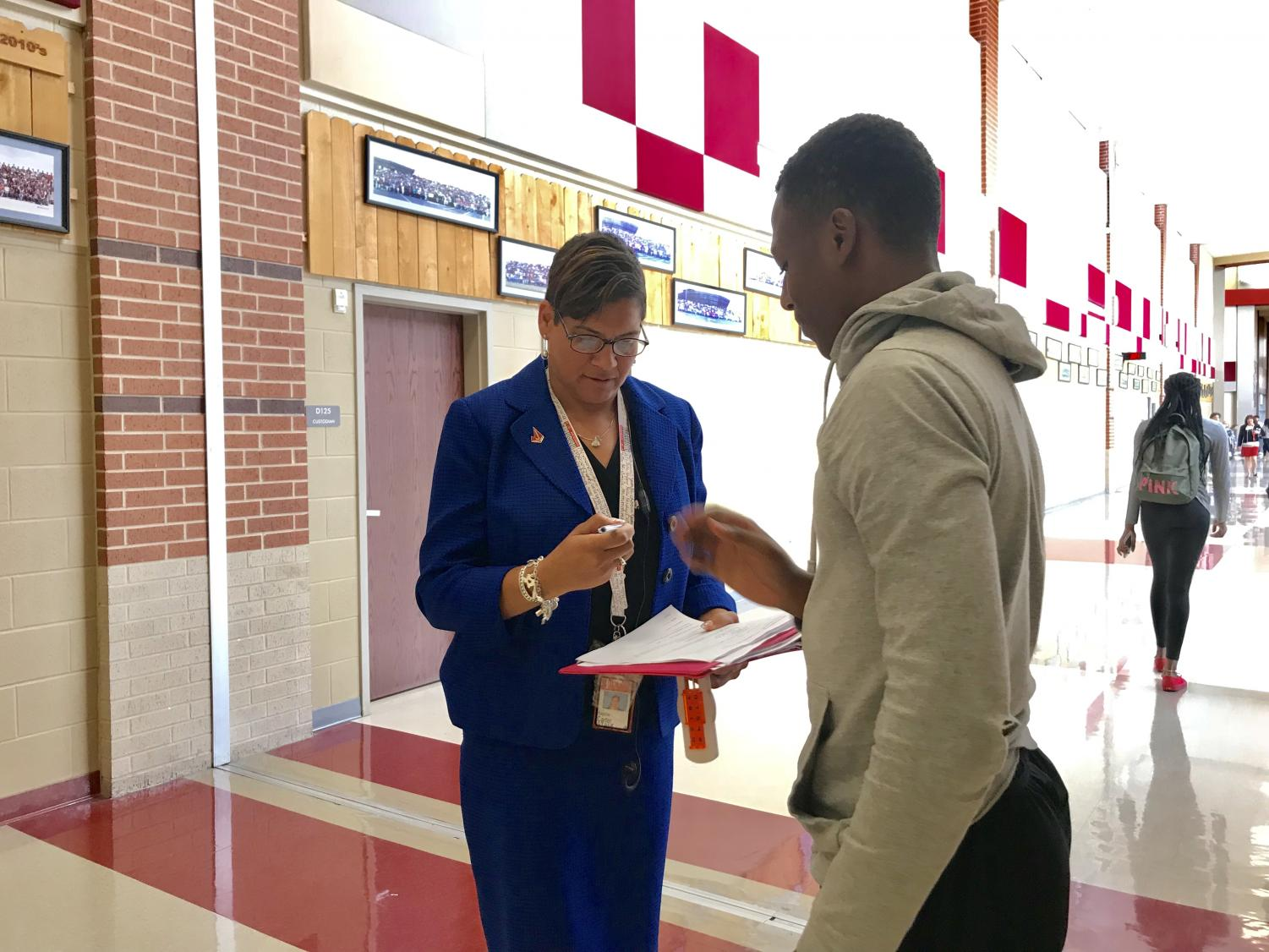 Carter signs student's form in the hallway. Carter attended Judson herself and graduated in the class of 1991.
