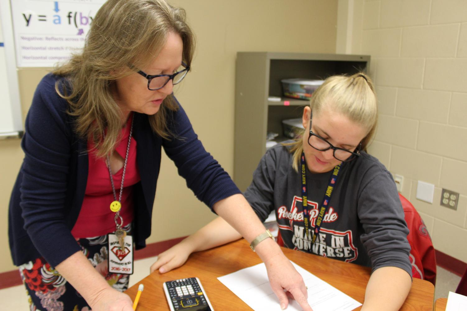 Mrs. Brenda Milam helps a student with her classwork during one of her AP Calculus periods. Milam has been teaching at Judson High School for 32 years.