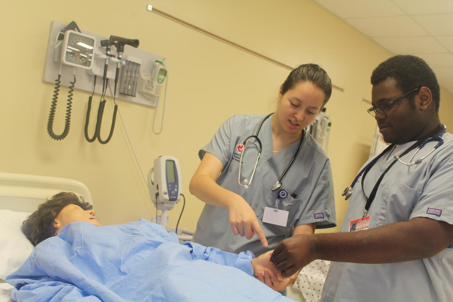 Two students examine a mannequin being used as a fake patient. Medical assistants are trained to deal with patient care.