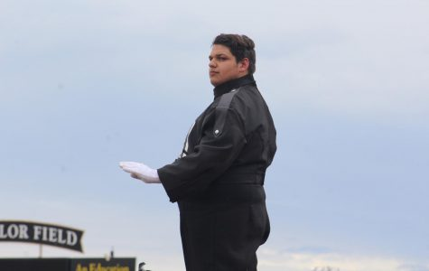 Junior Lonnie Buck looks out towards the field as he conducts. This is Buck's first year as a drum major.