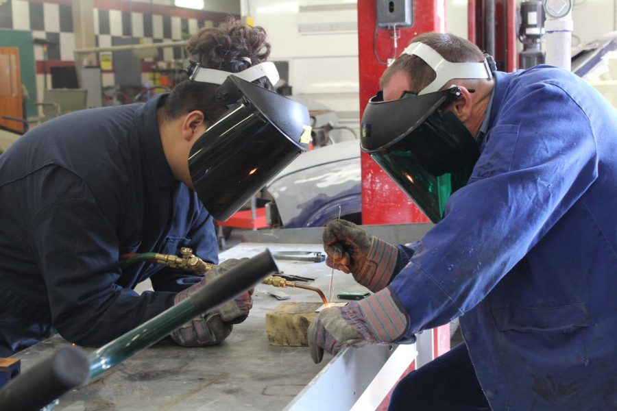 Auto+collision+teacher+Mr.+Kenneth+Turner+assists+student+in+welding+a+piece+of+sheet+metal+in+the+shop.+The+auto+collision+program+has+provided+program+has+taught+students+various+workplace+skills+alongside+welding.+