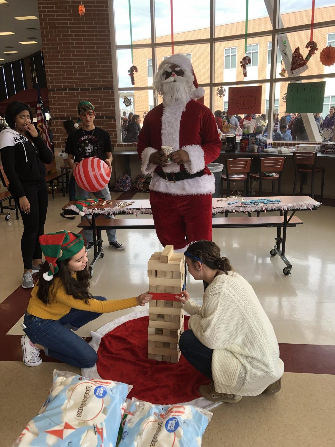 """The junior class officers and """"Santa"""" play Jenga at the Santa Workshop in the Cafeteria during lunch. The Santa Workshop worked as a fundraiser for project graduation."""