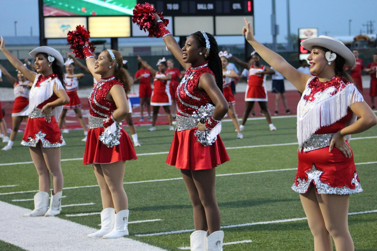 The dancers stand at attention before a football game at D.W. Rutledge Stadium. The move to combine the teams will make one varsity team and one true JV team.