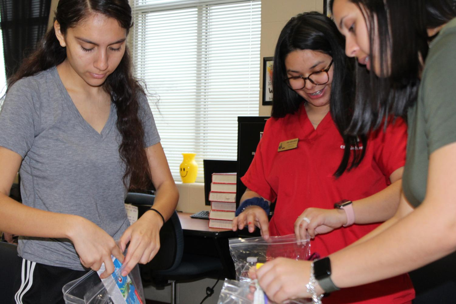 Senior Amorette Rodriguez, senior April Jacobo Gonzalez, and junior Maddie Lambert put different necessities into bags for those in need. This is the Student Council's first year collecting Blessing Bags.