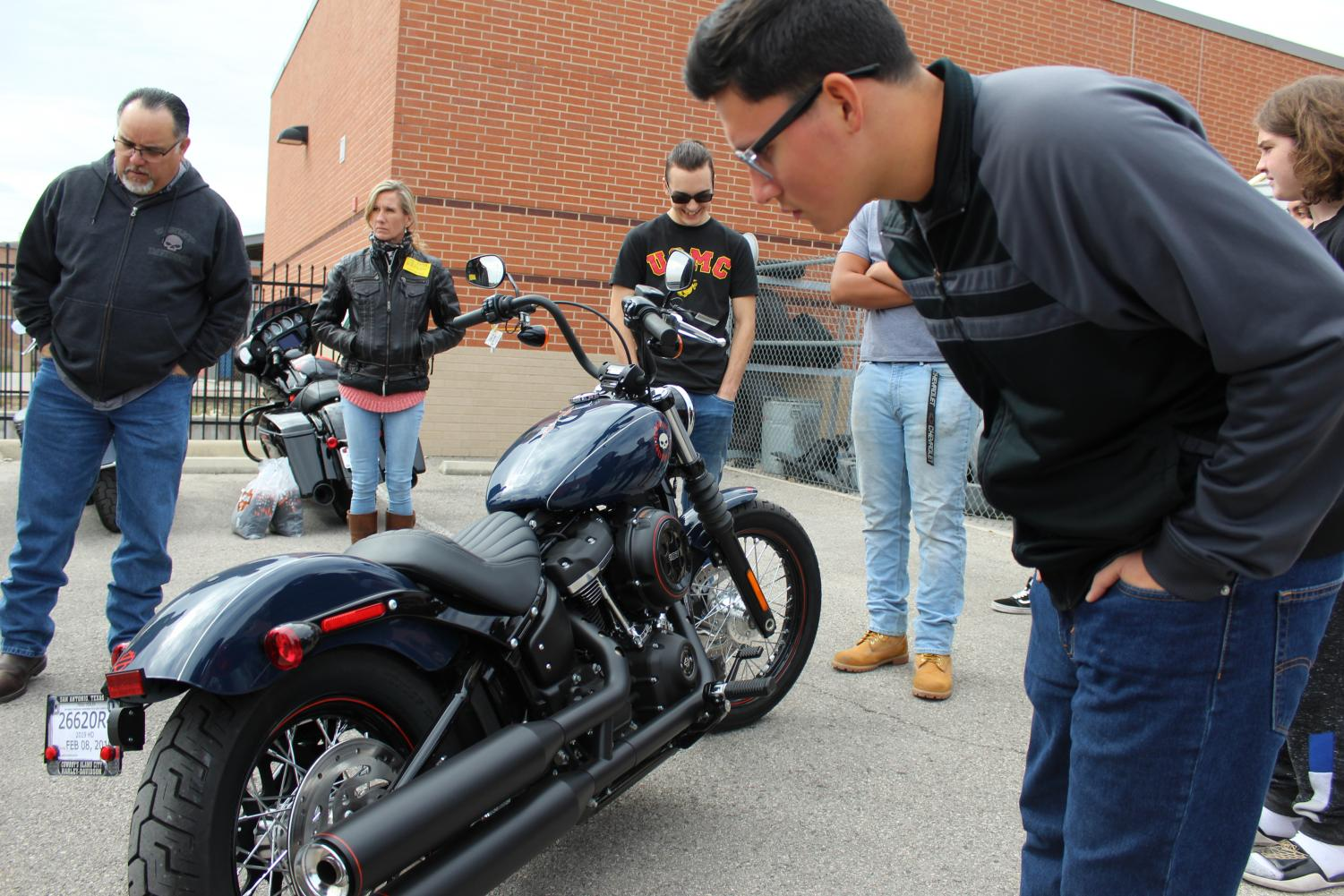 Automotive student examines motorcycle. The Harley-Davidson representatives brought several motorcycles for the students to look at before they started their own design.