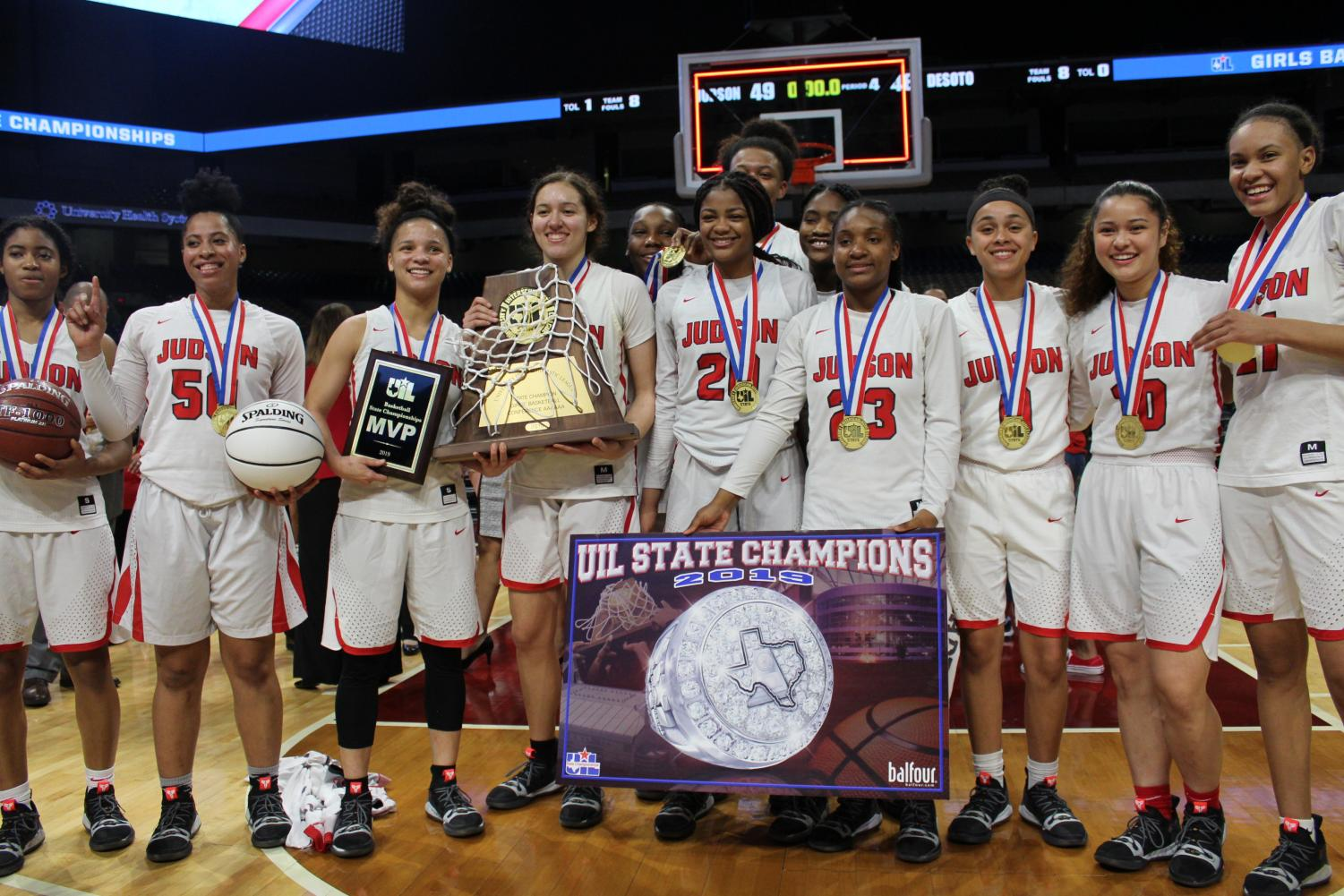 The 2018-2019 girls basketball team poses with their medals, plaque, and UIL 6A state championship poster for the media groups on the floor. This is the first girls basketball state championship at Judson.