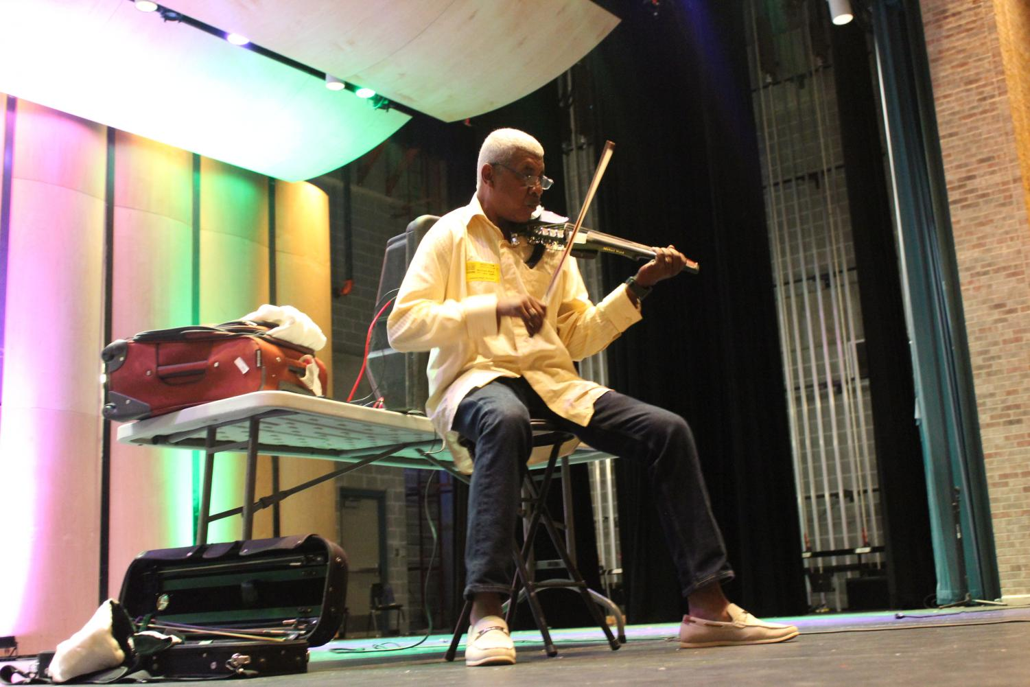 World-renowned musician Michael Ward plays his violin in front of band and orchestra members in the Performing Arts Center. Ward has traveled all over the world playing concerts for high profile people.