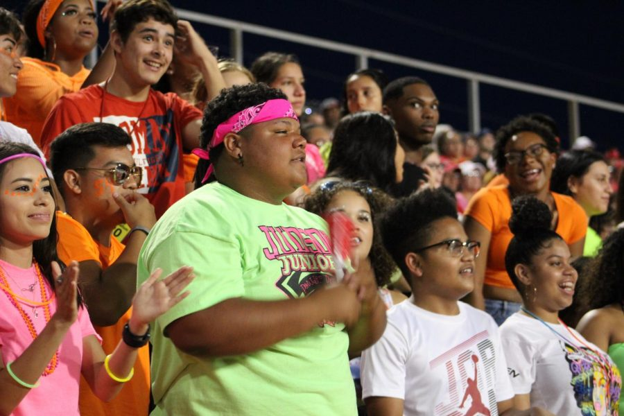 Senior+Calvin+Ashley+leads+the+student+section+during+the+Steele+game.+The+theme+of+the+game+was+neon+colors.