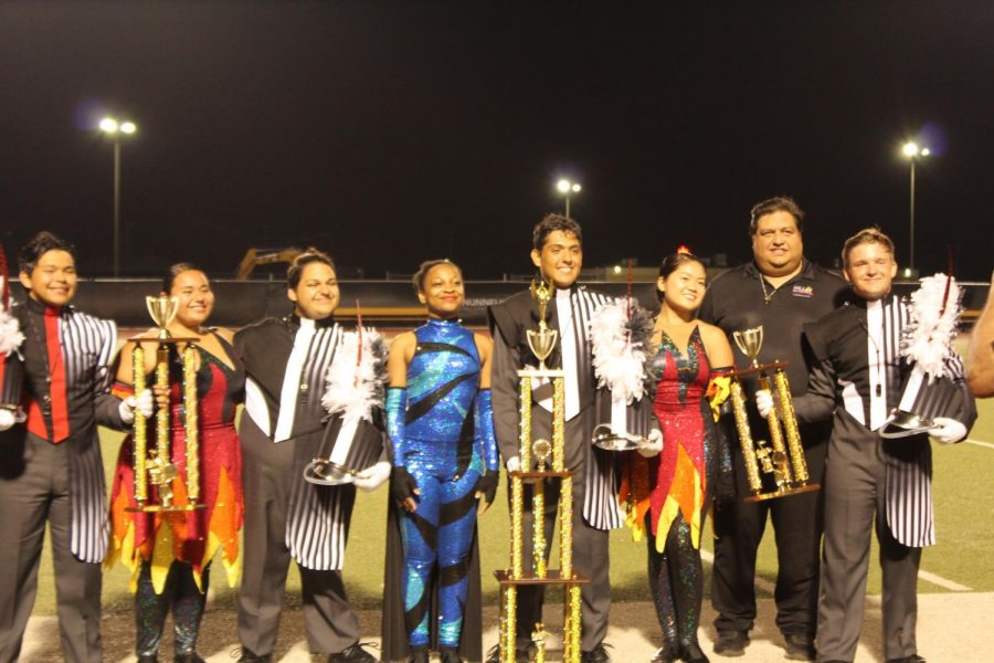 Drum+majors+and+colorguard+captions+stand+together+with+their+massive+6A+Championship+trophy.+This+is+the+first+of+three+competitions+for+the+band+this+season.