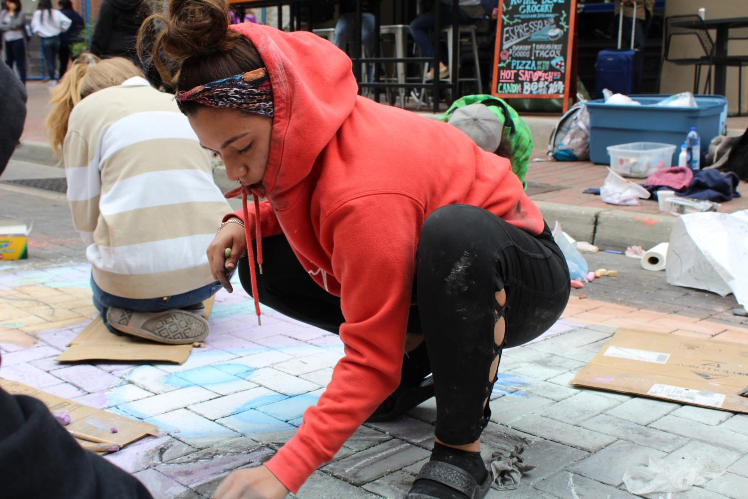 Senior Jacklyn Servin chalks up Houston Street in downtown San Antonio. This is the 5th year Art Club has participated in this event.