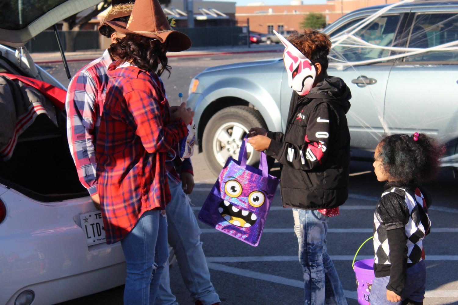 Neighborhood children come up to cars sponsored by campus organizations at the first annual Trunk or Treat.