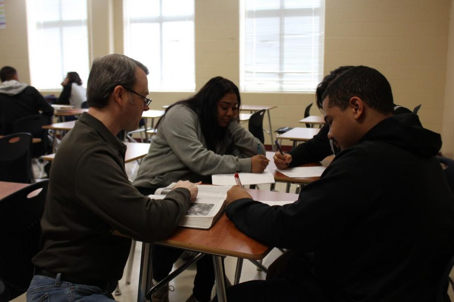 Mr. Hoxie (Left) works with a group of students in his US History class. This is his 14th year in the classroom.