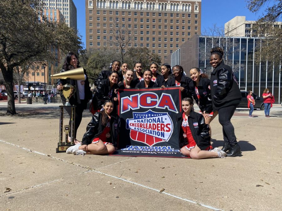 The cheerleaders pose with their national championship trophy and banner after their competition. This is the first time in 21 years the cheer team has brought back a national title to the campus.