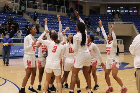 The girls basketball team celebrates in the middle of the court at Northside Athletics Gym. The girls will advance to the next round of the playoffs.