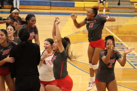 The volleyball team celebrates their win against Clemens.