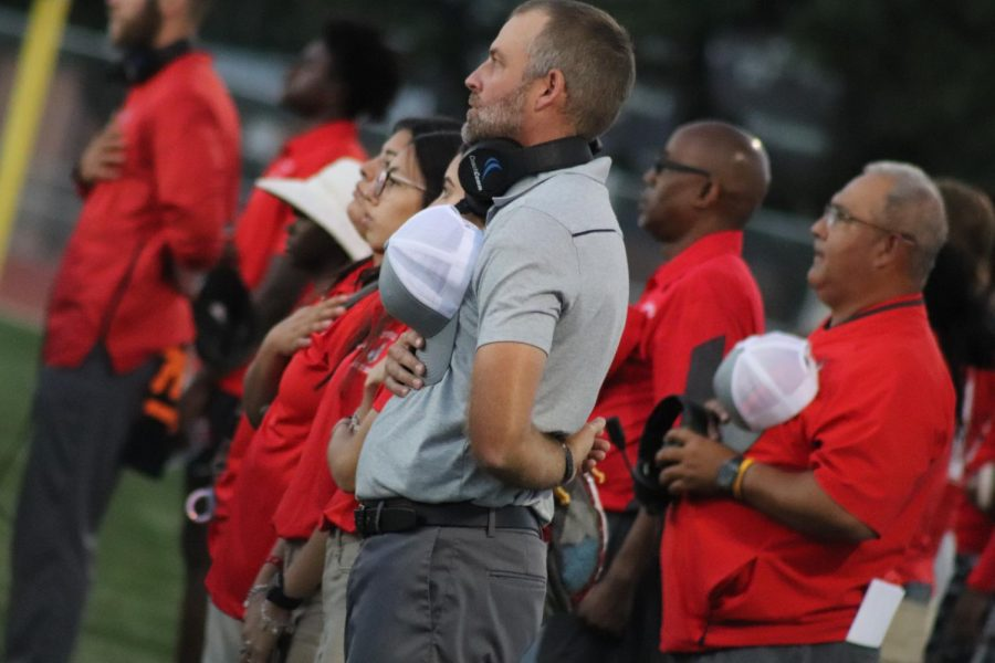 Coach Joel Calls holds his hat on his heart as the national anthem is played during the game against Smithson Valley. This was the first win of his career as head coach, beating Smithson Valley 33-32.