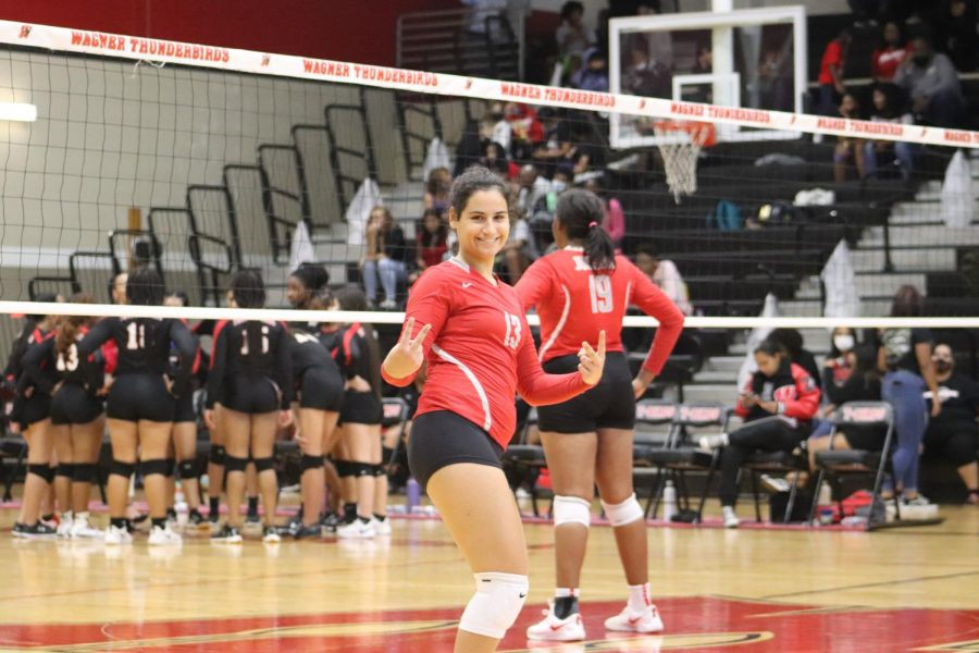 Junior Gaia Pescosolido smiles in between sets. When she was asked to pose, she made her signature smile and thumbs up during the game.